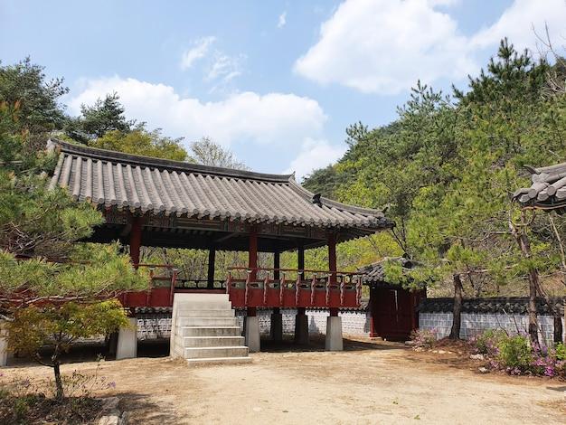 Traditioneel koreaans gebouw omgeven door bomen onder een blauwe lucht