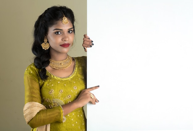 Traditioneel meisje dat en leeg wit tekenraad houdt toont