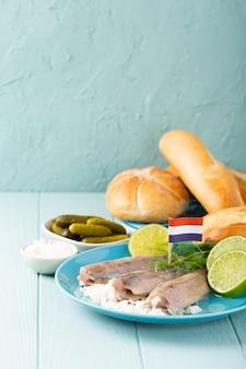 Traditioneel nederlands eten vers gezouten haringvis met ui genaamd hollandse nieuwe op turkooizen plaat en houten oppervlak. europees voedselconcept met exemplaarruimte