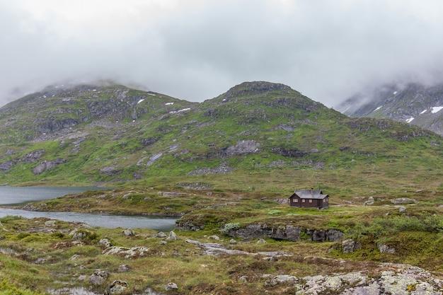 Traditioneel noors houten huis aan de oever van het meer en de bergen in de verte
