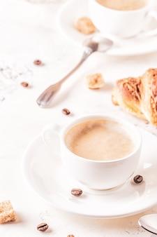 Traditioneel ontbijt met verse croissants op wit, verticaal.