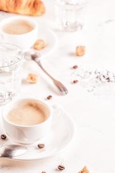 Traditioneel ontbijt met verse croissants op witte verticale achtergrond.