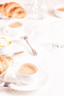 Traditioneel ontbijt met verse croissants op witte verticale achtergrond,.