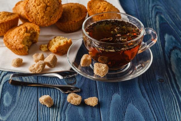 Traditioneel ontbijt met zwarte thee en croissants, vintage houten tafel