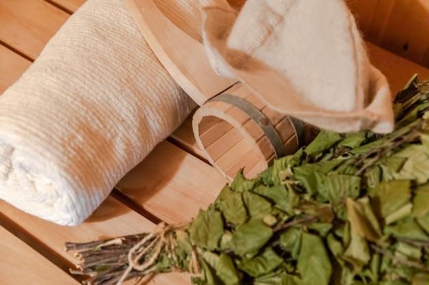 Traditioneel oud russisch badhuis spa-concept. interieur details finse sauna stoomcabine met traditionele sauna accessoires set handdoek berken bezem schepvilt. ontspan het badconcept van het landdorp.