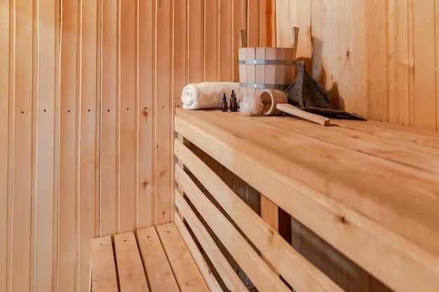 Traditioneel oud russisch badhuis spa-concept. interieur details finse sauna stoomcabine met traditionele sauna accessoires set wastafel handdoek aroma olie schep vilt. ontspan het badconcept van het landdorp.