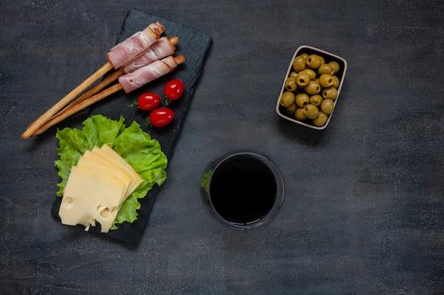 Traditioneel pancetta-spek geserveerd met gepekelde olijven, tomaten, groene slablaadjes, kaas, wijn en grissinibrood
