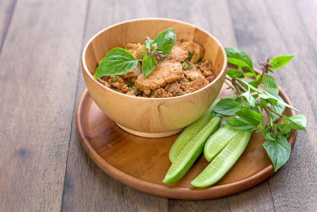 Traditioneel pittige gegrilde varkenssalade in thaise noordoost-stijl genaamd nam tok mho