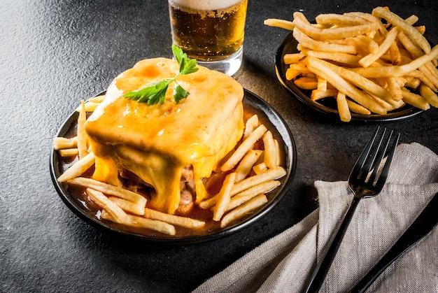 Traditioneel portugees snackvoedsel. broodje francesinha van brood, kaas, varkensvlees, ham, worstjes, met tomatensaus en frites. met een glas bier en aardappelen. op zwarte tafel. kopieer ruimte