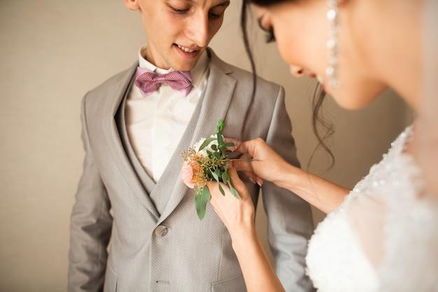 Traditioneel raakt de bruid in het huis een klein boeket aan voor de bruidegom, bruidegomboeket naast de hand op pak