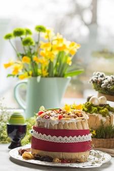 Traditioneel russisch pasen-kwarkdessert, orthodoxe paskha op lijst met kulichcakes, bloemen, gekleurde eieren.