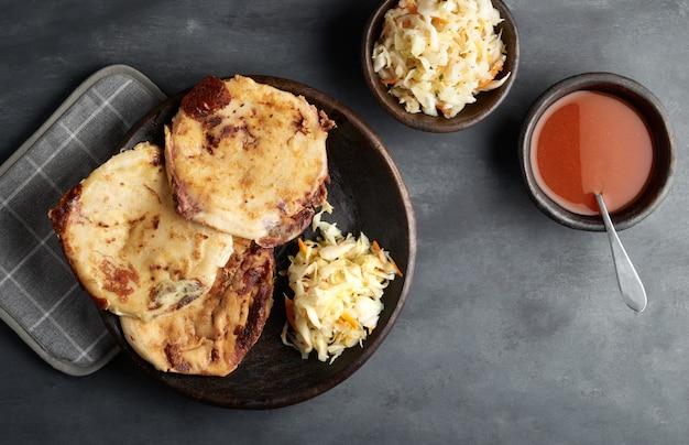 Traditioneel salvadoraans ontbijt en diner, maïstortilla's gevuld met varkensvlees, kaas en bonen, eten uit latijns-amerika