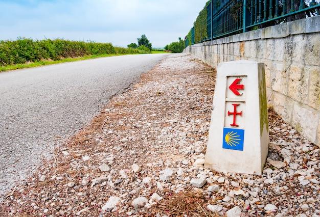 Traditioneel schelpteken en pijl onderweg geschilderd. richtingsteken voor pelgrims op de saint james-manier, camino de santiago de compostela, spanje
