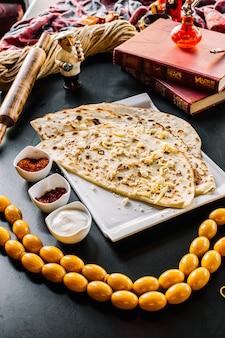 Traditioneel schotelvlees kutab met geraspte kaas op het hoogste sumakh berberis duidelijke youghurt zijaanzicht