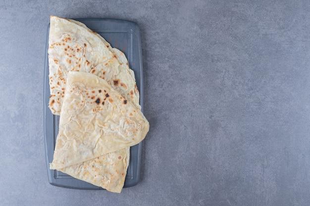 Traditioneel tarwe lavash brood op het houten dienblad op marmeren tafel.