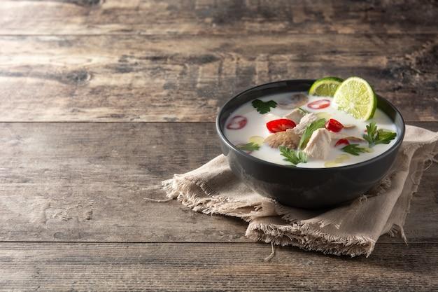 Traditioneel thais eten tom kha gai in kom op houten tafel