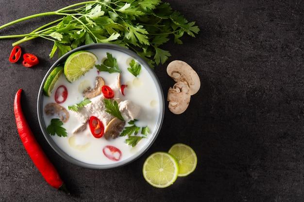 Traditioneel thais eten tom kha gai kokosmelk soep met kip, gember, chilipepers, limoen en champignons op zwart