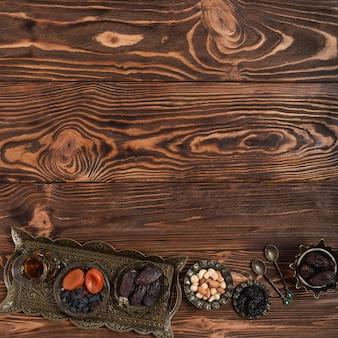 Traditioneel turks metaaldienblad met theeglas; gedroogde vruchten en noten op gestructureerde houten achtergrond met ruimte voor het schrijven van de tekst