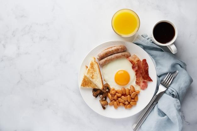 Traditioneel vet engels ontbijt heerlijke eieren spek worstjes champignons bonen en toast