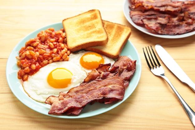 Traditioneel volledig engels ontbijt - gebakken eieren, bonen, spek en toast op bruine tafel.