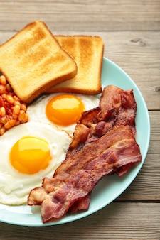 Traditioneel volledig engels ontbijt - gebakken eieren, bonen, spek en toast op grijze houten tafel