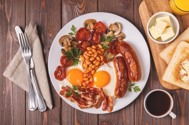 Traditioneel volledig engels ontbijt met gebakken eieren, worstjes, bonen, champignons, gegrilde tomaten en spek op houten achtergrond