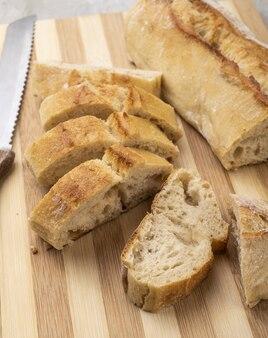Traditioneel zelfgemaakt frans stokbroodbrood met plakken over houten plank