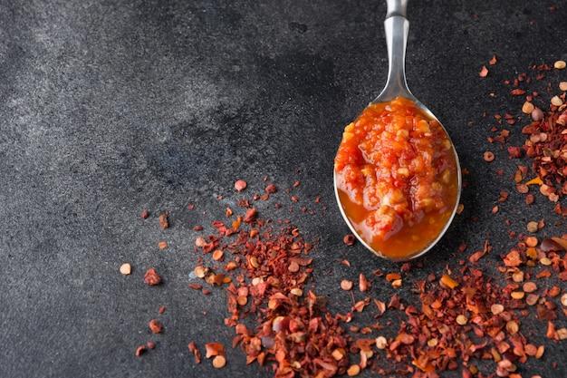 Traditionele adjika hete chili peper saus harissa plakken in lepel op zwart. tunesië, georgische en arabische keuken.