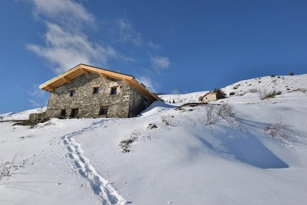 Traditionele alpine chalet op de top van besneeuwde berg onder de blauwe hemel