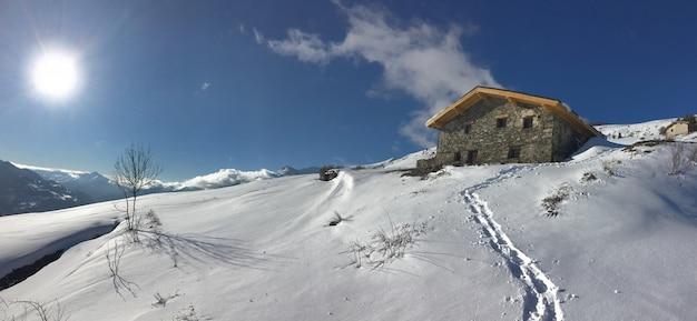 Traditionele alpine chalet op de top van besneeuwde berg onder zonsopgang in de lucht