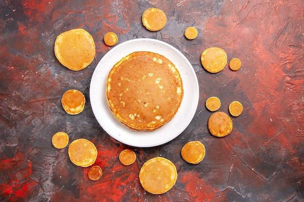 Traditionele amerikaanse pannenkoeken op plaat en tafel, bovenaanzicht
