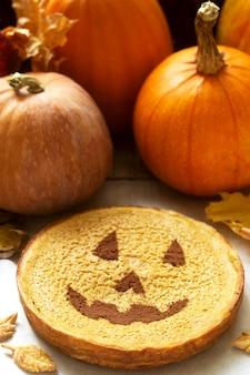 Traditionele amerikaanse pompoen zelfgemaakte cake versierd met cacao, pompoenen en herfstbladeren.