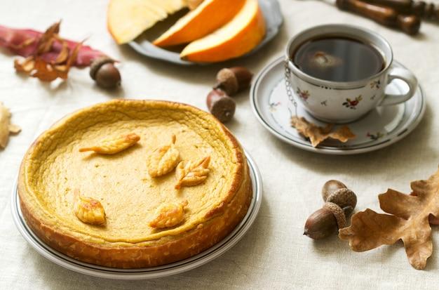 Traditionele amerikaanse pompoen zelfgemaakte cake, versierd met koekjes op een achtergrond van pompoenen en herfstbladeren.
