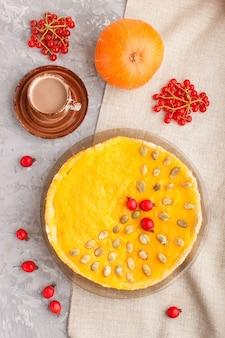 Traditionele amerikaanse zoete pompoenpastei die met meidoorn rode bessen en pompoenzaden wordt verfraaid met kop van koffie op een grijs beton. bovenaanzicht, close-up.