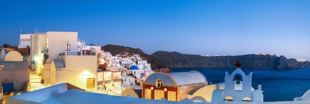 Traditionele appartementen en klokkentorens in oia, santorini, griekenland, in de avond