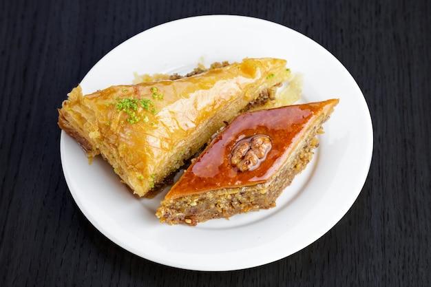 Traditionele arabische dessertbaklava met okkernoten en kardemom, op een houten lijst. zelfgemaakte baklava met noten en honing.