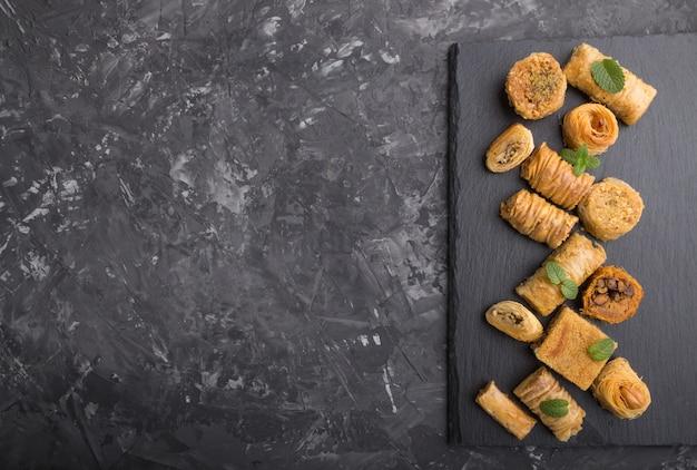 Traditionele arabische snoepjes (kunafa, baklava) op een zwarte lei boord. bovenaanzicht, copyspace.