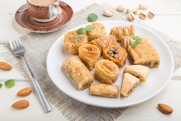 Traditionele arabische zoetigheden (kunafa, baklava) en een kopje koffie. zijaanzicht
