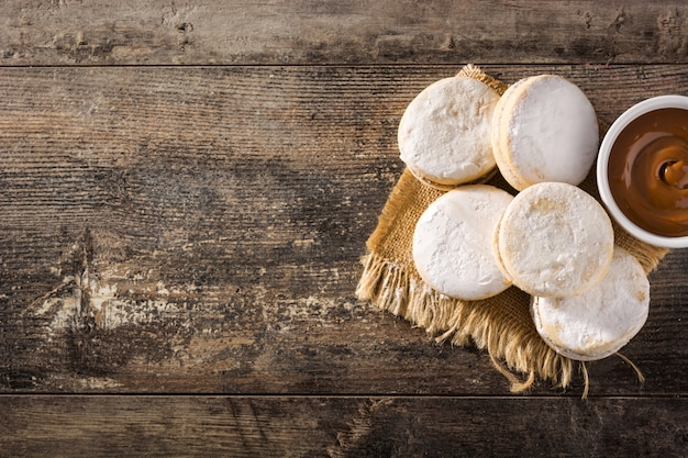 Traditionele argentijnse alfajores met dulce de leche en suiker op houten lijst, exemplaarruimte