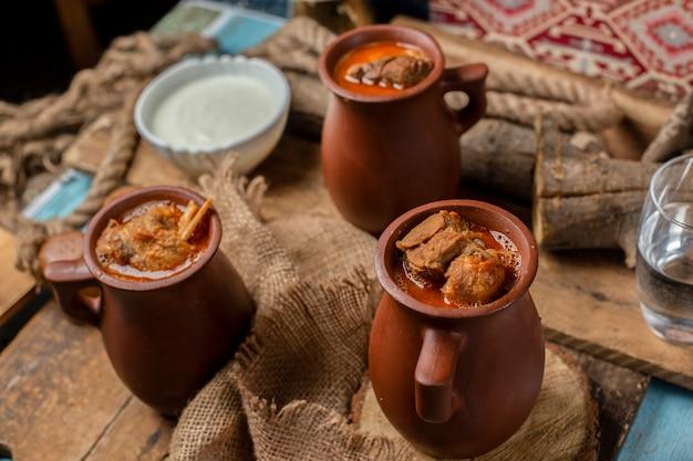 Traditionele azerbeidzjaanse maaltijd piti in aardewerkbekers.