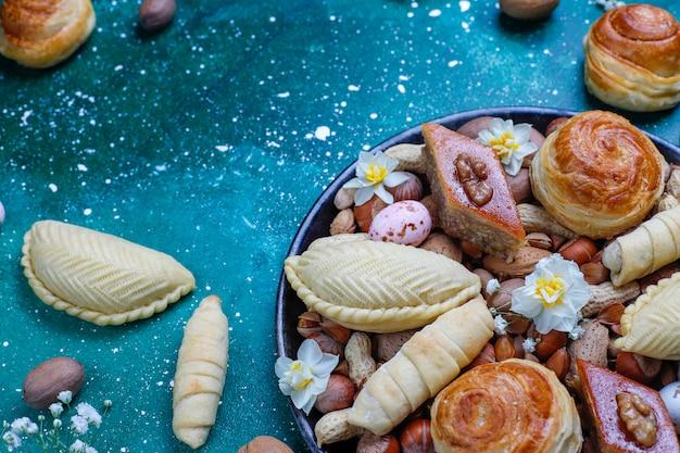 Traditionele azerbeidzjan vakantie novruz koekjes baklavas en shakarburas op zwarte dienbladplaat