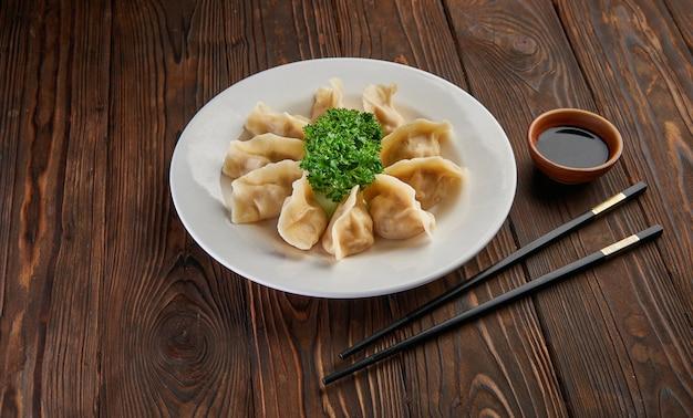 Traditionele aziatische gebakken dumplings gyoza op witte plaat en sojasaus met paar eetstokjes op donkere houten tafelblad bekijken en kopie ruimte