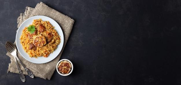 Traditionele aziatische schotel - pilaf van rijst, groenten en vlees in een bord op zwarte achtergrond. bovenaanzicht. lang formaat.