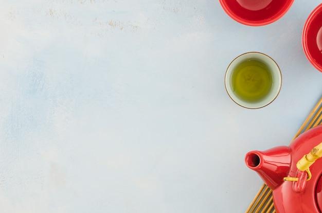 Traditionele aziatische theepot en theekopjes die op witte achtergrond worden geïsoleerd