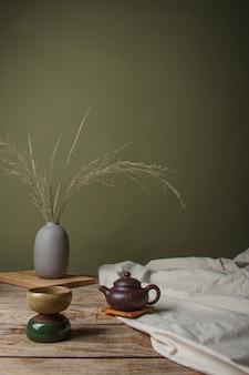 Traditionele aziatische theeset - keramische theepot en theekopjes voor theeceremonie op een houten tafel.