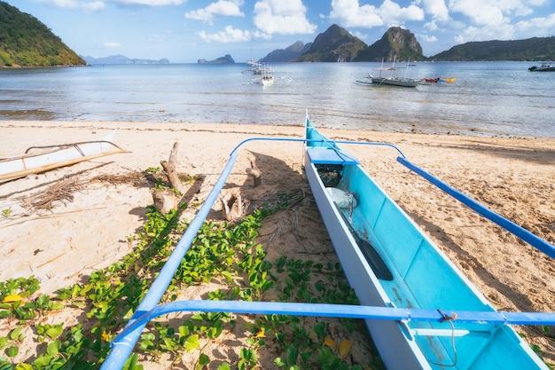 Traditionele banca-boot bij zandig strand. ondiepe lagune en kustlijn van el nido op achtergrond. palawan, filippijnen.