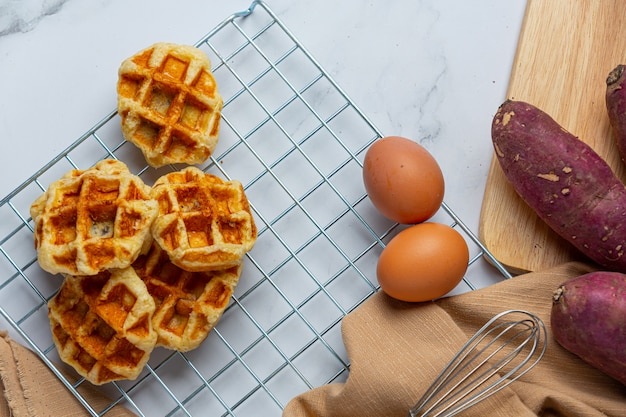 Traditionele belgische wafels, bloedsinaasappelen en bosbessen dressing en kopje koffie voor zoet ontbijt, samenstelling op lichte achtergrond.