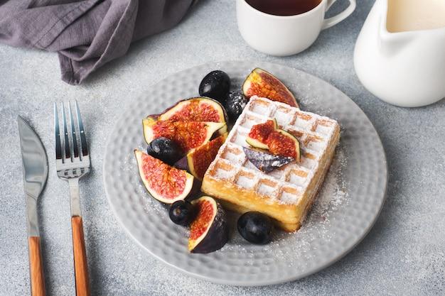 Traditionele belgische wafels met poedersuikerdruiven en vijgen.
