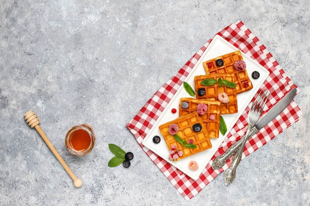 Traditionele belgische wafels met verse bessen en honing op grijze betonnen ondergrond.