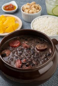 Traditionele braziliaanse feijoada met rijst, sinaasappel, cracklings, peper en caipirinha.